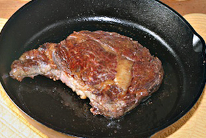 cooking rib eye steak in a cast  iron skillet